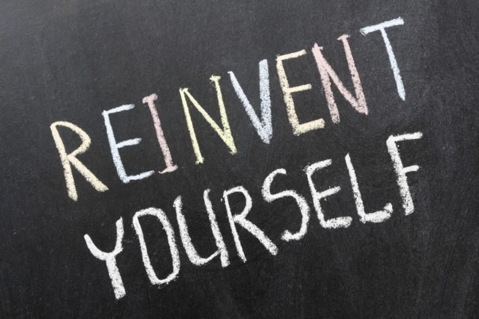 reinvent yourself phrase handwritten on school blackboard